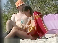 Dark haired nudist spied pissing on the beachvoyeur voyeur