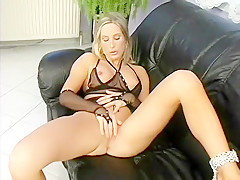 Striking blonde in black lingerie lies on the couch and pleases herself