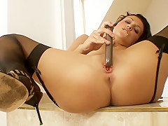 Sweet brunette in black stockings has a sex toy making her slit happy